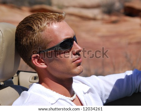A handsome young man driving a sports car in the southwest - stock photo