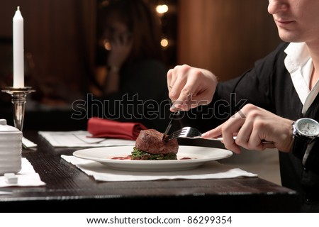 A handsome young man eating delicious meat cutlet with a knife and fork at a table elegantly served - stock photo