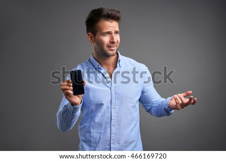 A handsome young man feeling frustrated and showing his phone to the camera.