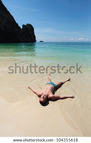 A handsome young man lying in the clear water at the beach seashore - stock photo