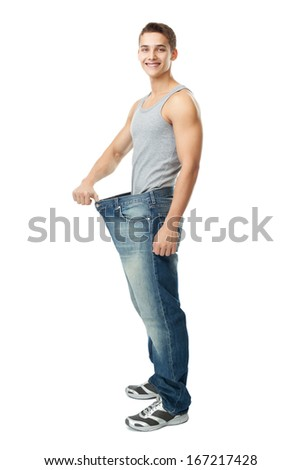 A handsome young man showing how much weight he lost isolated on white background - stock photo