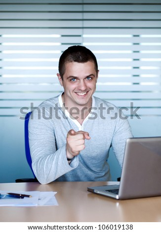A handsome young man sitting at the table with a laptop and pointing his index finger at others - stock photo