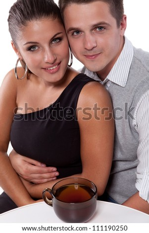 A handsome young man with a beautiful woman sitting at the table with a large cup of tea - stock photo