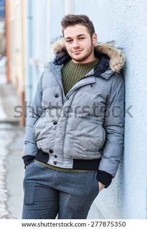 a handsome young man with winter clothes strolling in a small mountain town in europe - stock photo