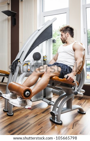 A handsome young muscular sports man doing leg press - stock photo