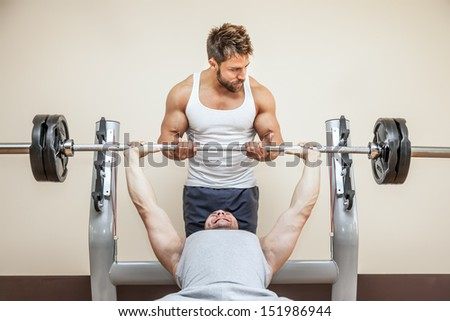 A handsome young muscular sports man doing weight lifting and gets help from his friend - stock photo