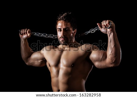 A handsome young muscular sports man with a chain - stock photo
