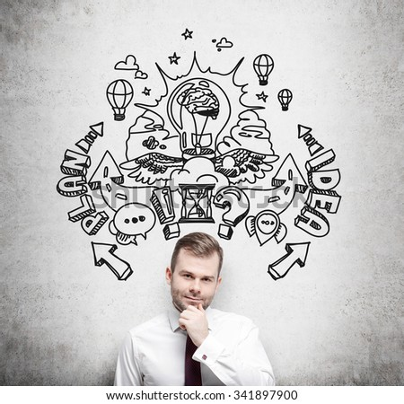 A handsome young professional is forecasting a building of a business plan for business development. Business plan sketch is drawn on the concrete wall behind the person. - stock photo