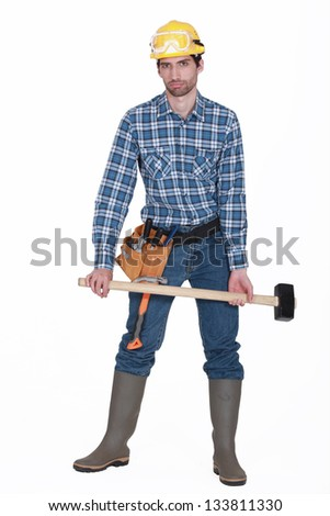 A handyman with a sledgehammer. - stock photo