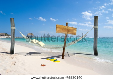 A hanging hammock, a wooden sign post , thongs and starfish on a beach resort - stock photo