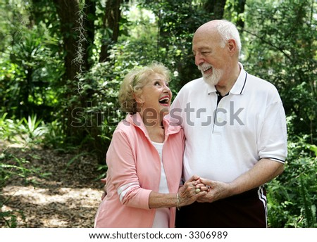 A happy, active senior couple laughing together on a walk through the park.  She's wearing a hearing aid.  Plenty of copy space. - stock photo