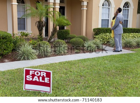 A happy African American man and woman couple house hunting outside a large house with a For Sale sign - stock photo