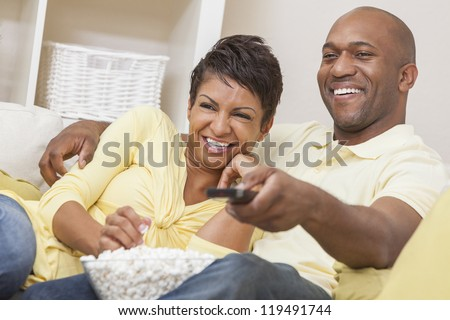 A happy African American man and woman couple in their thirties sitting at home, eating popcorn and using remote control watching a movie or television - stock photo