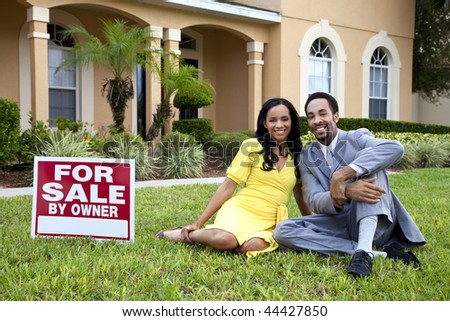 A happy African American man and woman couple outside a large house with a For Sale sign