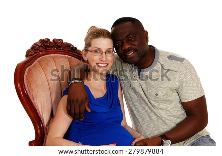 A happy African American man with his Caucasian wife sitting in a pink armchair, she is pregnant, isolated for white background.  - stock photo