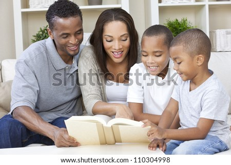 A happy African American man, woman and boys, father, mother and two sons, family sitting together at home reading a book - stock photo