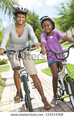 A happy African American woman and child, mother & daughter, cycling together. - stock photo