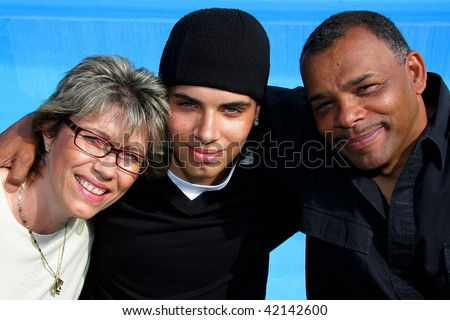 a happy American-German family with mother, father and son photographed in the summer sun with a swimming pool in the background - stock photo