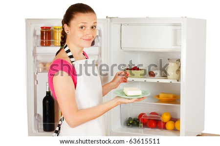 A happy and attractive young woman in a pinafore dress using the refrigerator - preparing for cooking. - stock photo