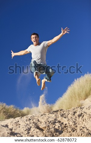 A happy and excited young man jumping high with arms outstretched on a sunny sandy beach with blue sky