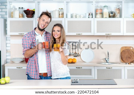 A happy and healthy life. Young couple in love drinking hot tea while standing in the kitchen and cooking and holding a cup looking and smiling at the camera - stock photo