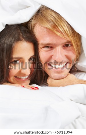 A happy and romantic couple do pose on bed