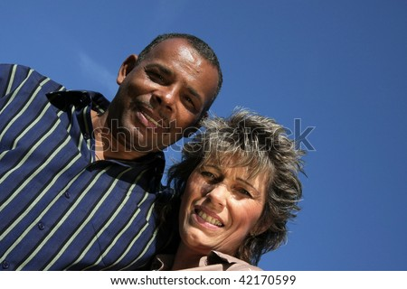 a happy and smiling American-German married couple photographed in the summer sun with blue sky and tiny clouds in the background - stock photo
