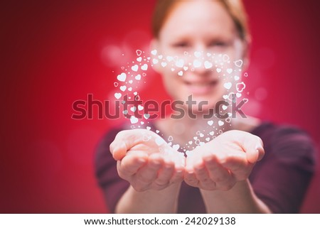 A happy and smiling young woman gives a heart as a gift, photographed on red background. - stock photo
