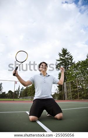 A happy asian male tennis player in joy after winning - stock photo