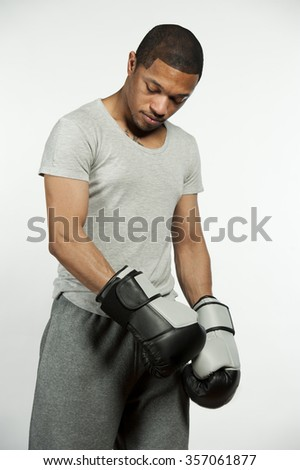 A happy attractive African American male wearing sweatpants and pro boxing gloves posing in a studio setting on a white background.