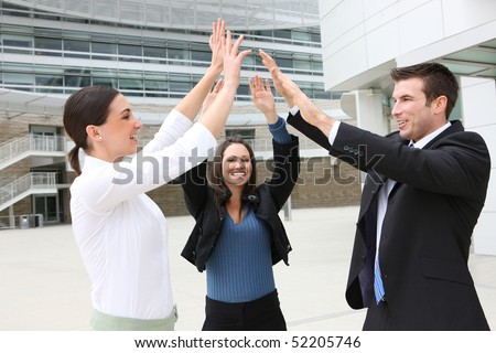 A happy attractive man and woman business team celebrating at office building