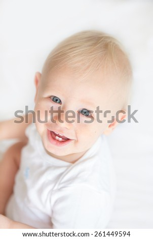 A happy baby boy with blond hair and blue eyes smiling up at the camera against a white background
