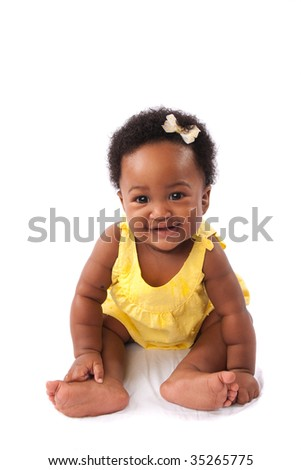 a happy baby smiling as she sits on white fabric - isolated except for the area she is sitting in - stock photo