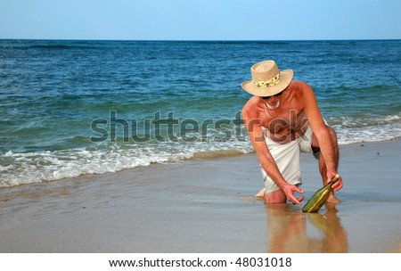a happy beach comber finds a message in a bottle - stock photo