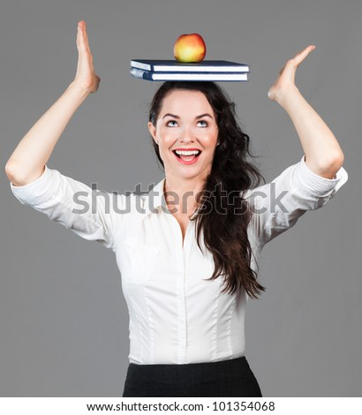 A happy beautiful business woman balancing books and an apple on her head - stock photo