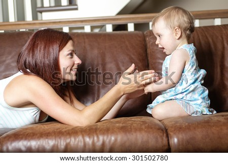 A happy beautiful young mother and baby laying on sofa