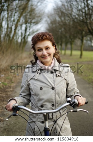 A happy beautiful young woman is having fun riding a bicycle.