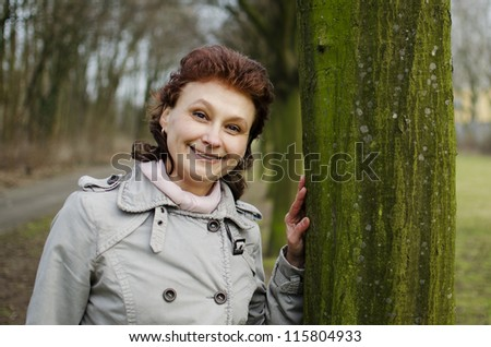 A happy beautiful young woman is smiling in a park, leaning on a tree.