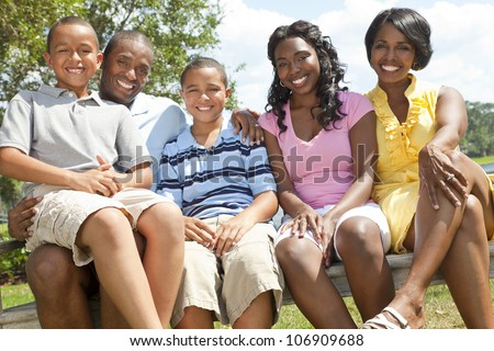 A happy black African American family of two parents and three children, two boys one girl, sitting together outside. - stock photo