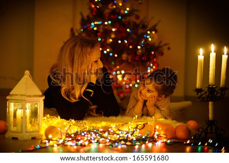 A happy blonde mother and her little daughter lying on the floor and looking at each other by the light of burning candles against the Christmas tree