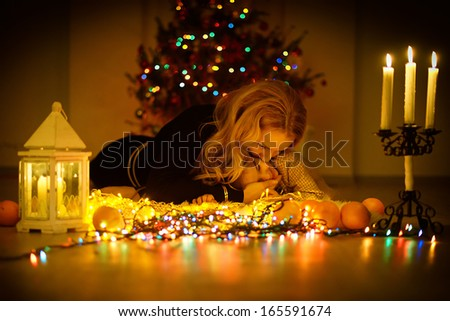 A happy blonde mother kissing and hugging her little daughter lying on the floor by the light of burning candles against the Christmas tree