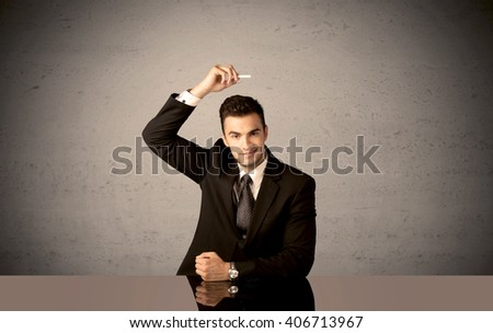 A happy businessman sitting at desk in front of clear grey empty background and drawing around himself with a white chalk concept
