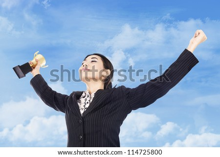 A happy businesswoman celebrating her winning with trophy in hand - stock photo