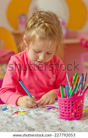 A happy charming child with crayons