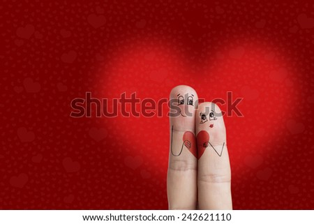 A happy couple in love with painted smiley and hugging. Happy Valentine's Day theme series. There are path included in image. You can easily cut out fingers from the background.  - stock photo