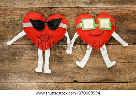 A happy couple in love with  smiles and sunglasses holding hands over wooden background - stock photo