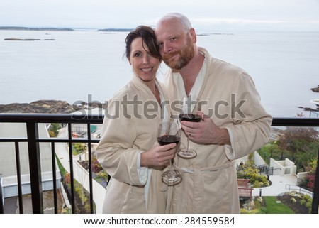 A happy couple on vacation with wine and a view - stock photo