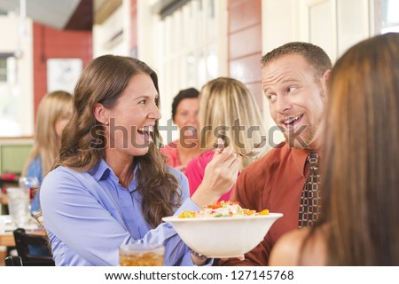 A happy couple sharing lunch at a restaurant. - stock photo