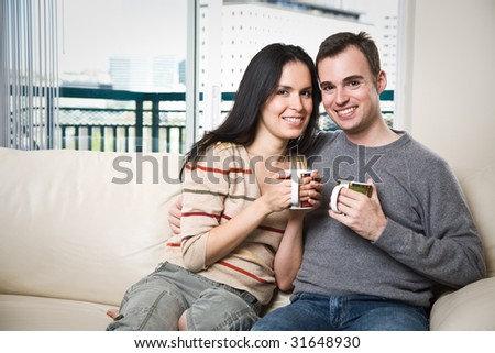 A happy couple sitting on the couch at home enjoying coffee - stock photo