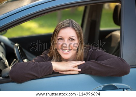 A happy driver leaning out of the window - stock photo